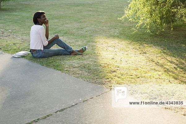 Entspannende junge Frau im Park mit Handy