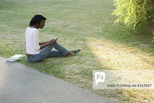 Entspannende junge Frau im Park  Text-messaging mit Handy