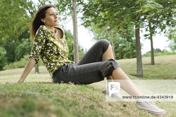 Frau sitzt auf Gras im Park  Wegsehen in Gedanken Frau sitzt auf Gras im Park, Wegsehen in Gedanken