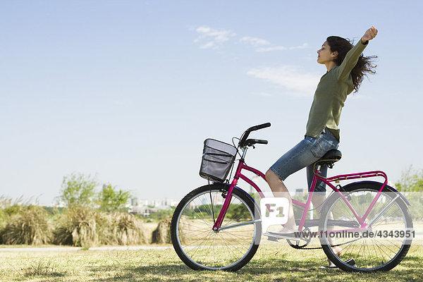 Junge Frau sitzt auf dem Fahrrad mit Waffen aus und geschlossenen Augen Junge Frau sitzt auf dem Fahrrad mit Waffen aus und geschlossenen Augen