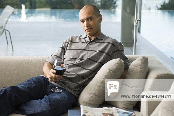 Mann auf Sofa mit Glas Wein entspannen Mann auf Sofa mit Glas Wein entspannen