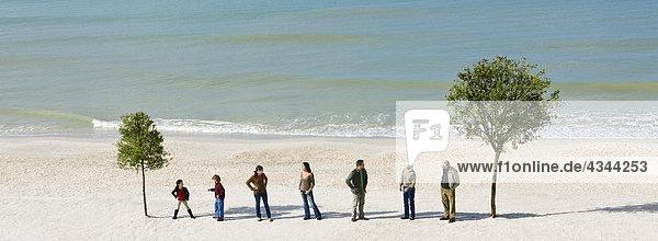 Gruppe von Personen stehen in Zeile Chat zwischen zwei Bäumen am Strand