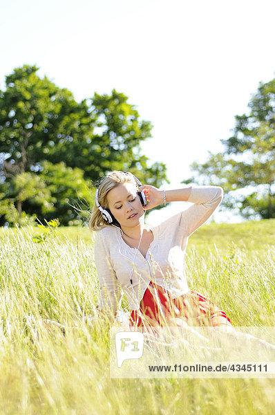 Junge Frau sitzt im hohen Gras und hört Kopfhörer.
