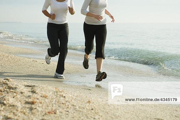Weibliche Freunde  die am Strand rennen  beschnitten
