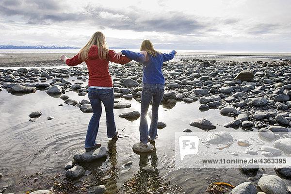 Zwei junge Frauen Fuß über Felsen am Bishop's Beach in Homer  Alaska