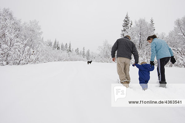 Couple take young son for an outdoor walk during Winter in Pedro Bay  Alaska.