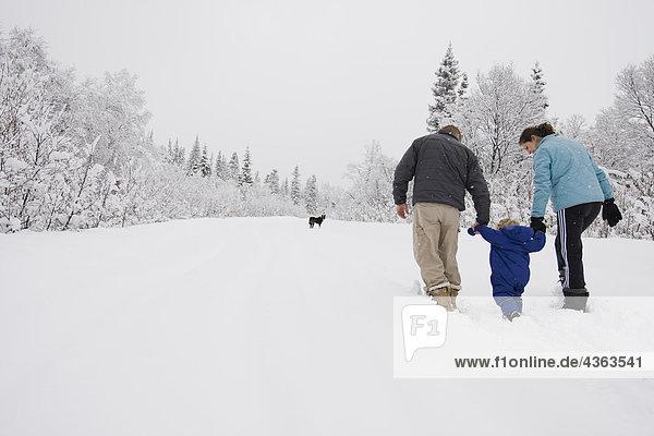 Einige dauern jungen Sohn für eine outdoor Spaziergang im Winter in Pedro Bay  Alaska.