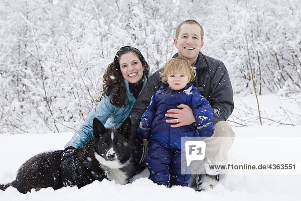 Young family pose for portrait during an outdoor walk in Winter in Pedro Bay  Alaska.