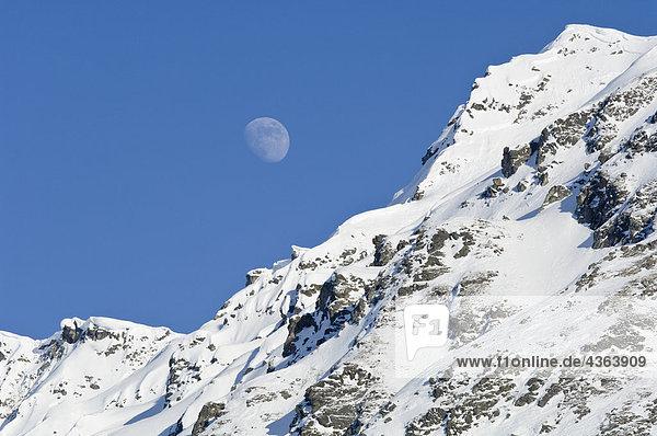 Moon Rising über Schnee bedeckte Gipfel am Hatcher Pass in South Central Alaska Moon Rising über Schnee bedeckte Gipfel am Hatcher Pass in South Central Alaska