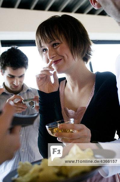 Junge lächelnde Frau mit Glas Champagner  Mann mit Digitalkamera im Hintergrund