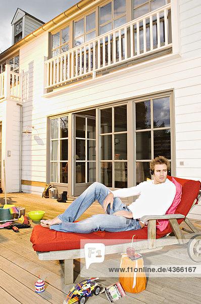 Junger Mann mit Kopfhörer auf einem Liegestuhl liegend