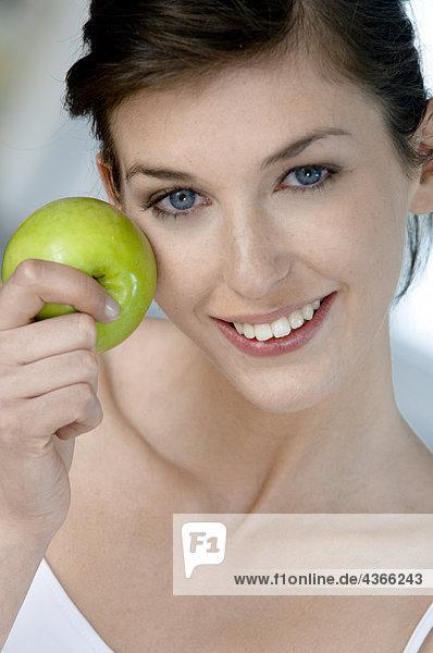 Porträt einer jungen Frau beim Apfelessen