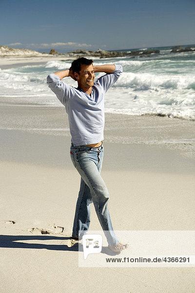 Mann  der am Strand spazieren geht