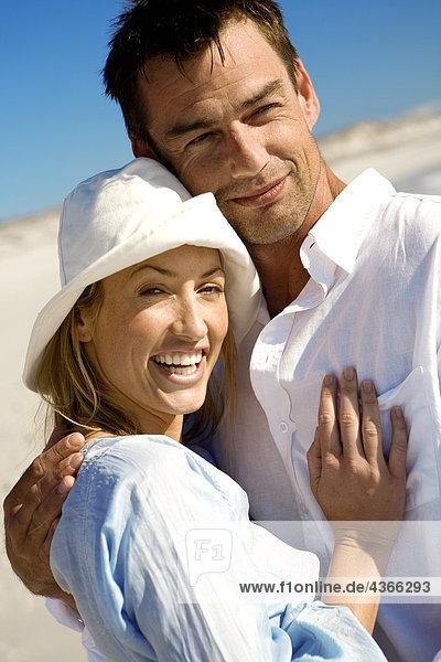 Porträt eines umarmenden Paares am Strand