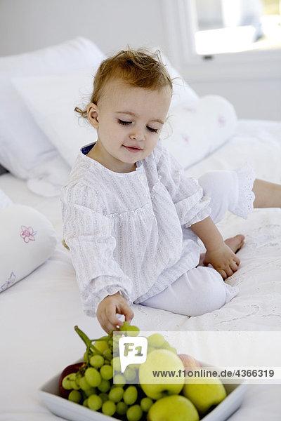 Kleines Mädchen  das auf einem Bett sitzt und Trauben nimmt.