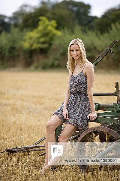 Eine Frau sitzend auf Landtechnik in eine abgeschöpfte wheatfield