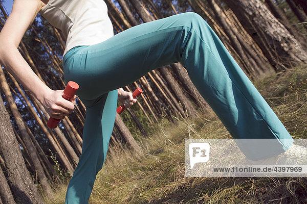 Detail der Frau macht stretching-Übungen im Wald Detail der Frau macht stretching-Übungen im Wald