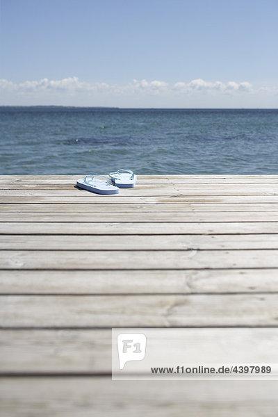 paar Flip flops auf hölzerne Pier an den Ozean