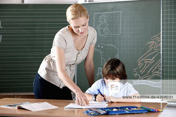 weibliche Lehrer helfen jungen Schüler in der Schule