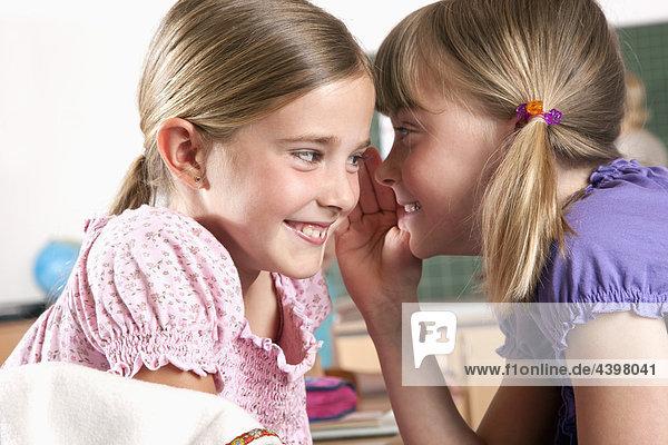 zwei junge Mädchen Flüstern zueinander im Klassenzimmer