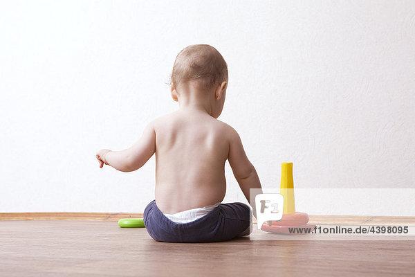 Rückansicht des Baby Junge spielt mit Spielzeug im Wohnzimmer