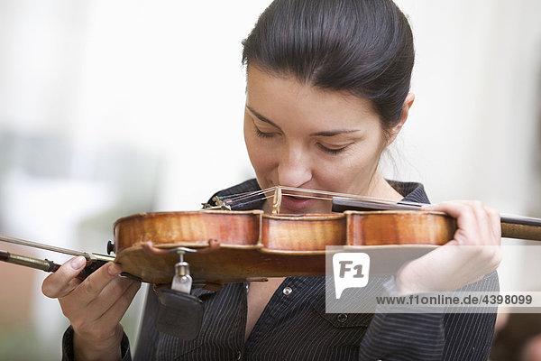Portrait des weiblichen Geigers küssen ihr instrument
