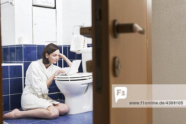 junge Frau mit Laptop-Computer im Badezimmer