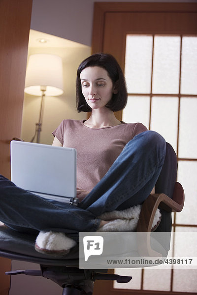young woman sitting at home working with laptop computer