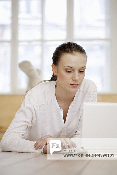 junge Frau auf Boden arbeiten mit Laptop-Computer liegen