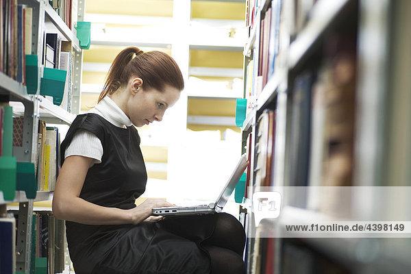 junge Frau mit Laptop-Computer in Bibliothek