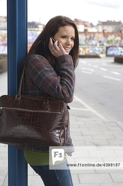 junge Frau an der Haltestelle sprechen auf Handy