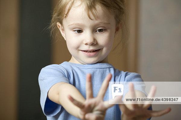 Porträt des kleinen Mädchens Blick auf ihre Hände