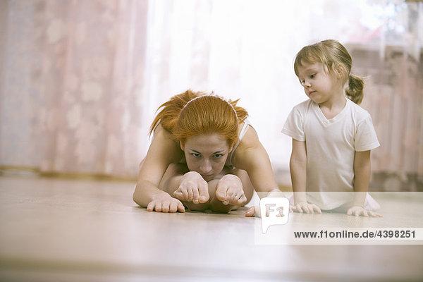 kleines Mädchen beobachten ihre Mutter tun stretching-Übungen kleines Mädchen beobachten ihre Mutter tun stretching-Übungen