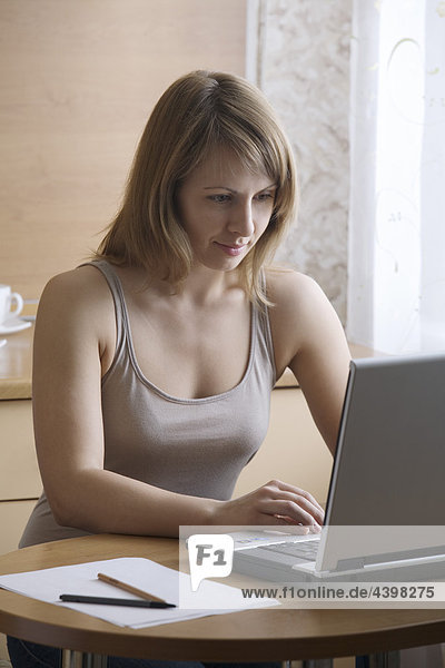young woman working with laptop computer at home