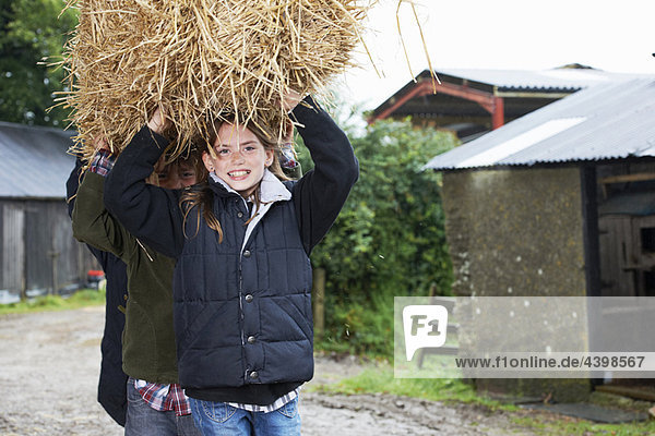 Children carrying straw bale on farm