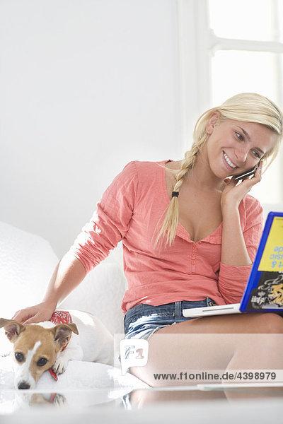 Junge Frau am Handy mit Laptop