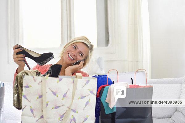 Frau am Telefon hält neue Schuhe zu Hause.