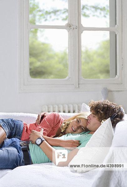 Junges Paar entspannt auf der Couch zu Hause