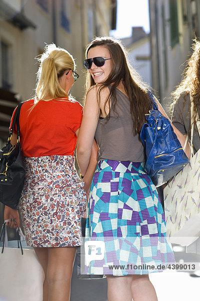 Freundinnen kaufen in Straßen mit Taschen ein