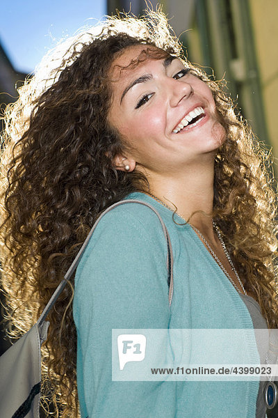 Portrait young woman laughs in street