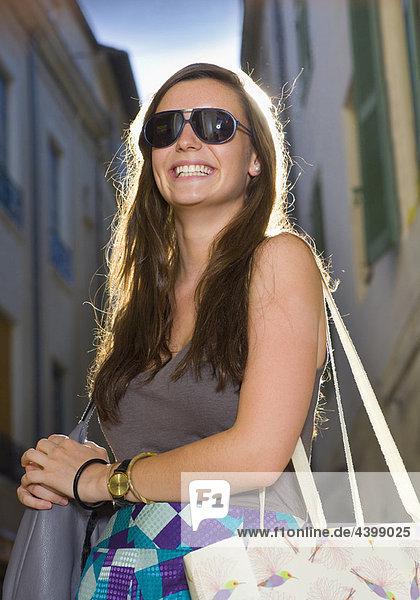 Portrait junge Frau in der Straße mit Taschen