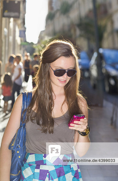 Junge Frau überprüft Handy in der Straße