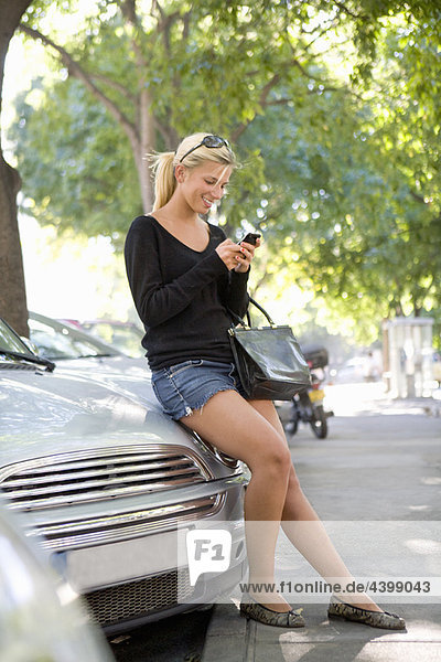 Young woman checks cell phone by car