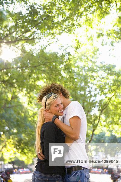 Junges Liebespaar umarmt sich im Freien