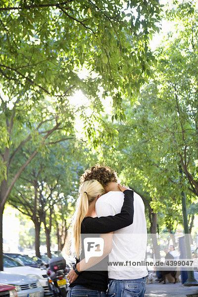 Liebende junge Paare umarmen sich auf der Straße