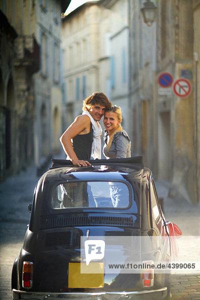 Paar hebt sich vom Schiebedach des Autos ab
