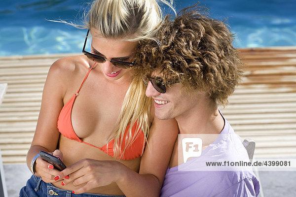 Junges Paar am Pool  Blick auf Telefon