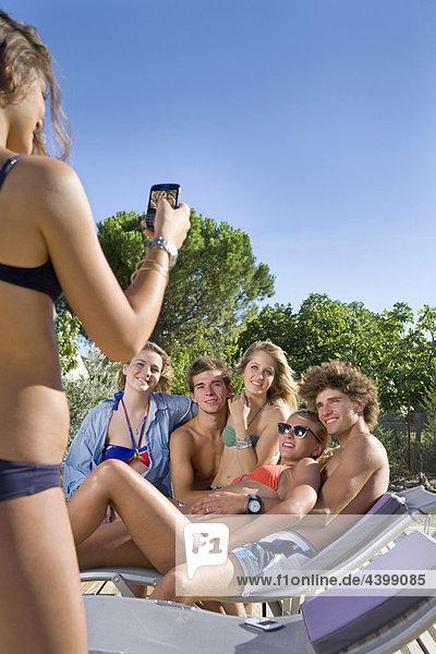 Teenager macht Telefonfoto der Gruppe in der Sonne