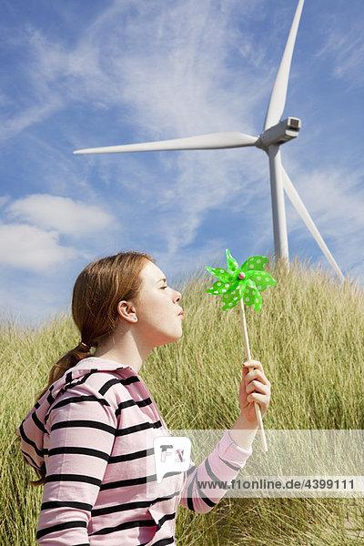 Mädchen bläst kleine Windmühle am Strand