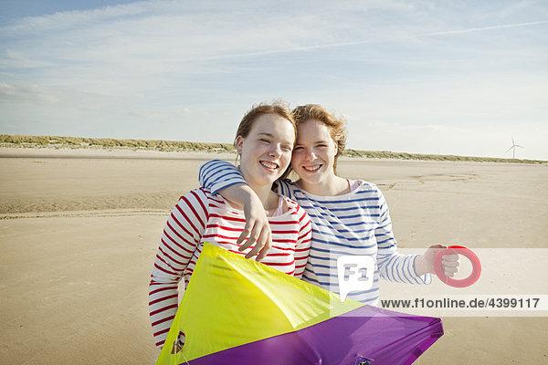 Zwei Mädchen mit Drachen am Strand